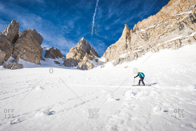 Man skiing up steep snowy section under mountains in California