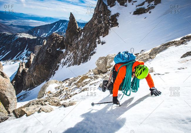 Man climbing up speed snow gully in California with rope
