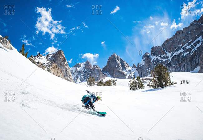 Man snowboarding down from mountain ridge in California backcountry