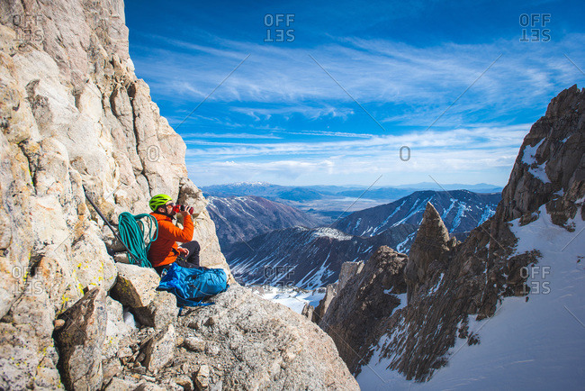 Climber drinking water on side of mountain in California backcountry