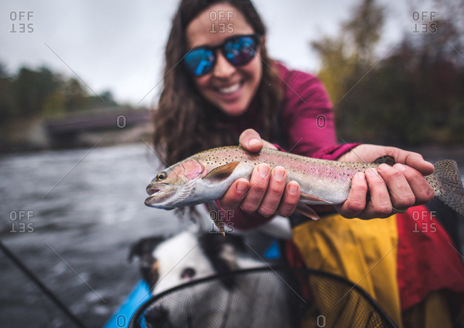 Woman smiling while holding a rainbow trout in boat