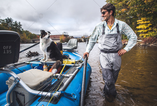 Man holding onto boat in river with dog in boat looking back