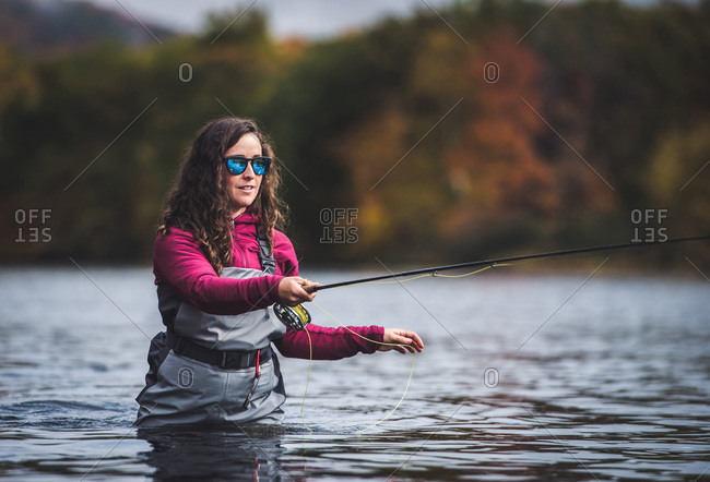 Woman angler in waders strips fly-line from her fly-rod while fishing