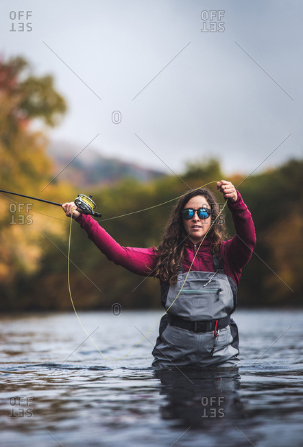 Woman in waders casting in river with fall foliage behind her