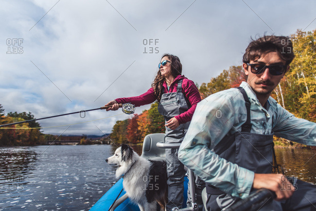 Man and woman anglers with dog in a boat during foliage season