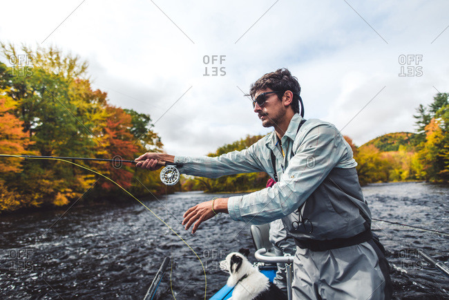 Fly fisherman casting from boat in river during fall foliage season