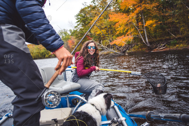 Woman in waders smiles after netting a fish in fall foliage