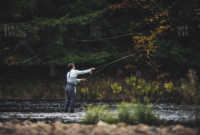 Male angler casts into river with dark background in the fall