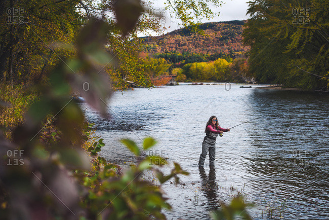 Woman in waders casts upstream during fall foliage season in NH