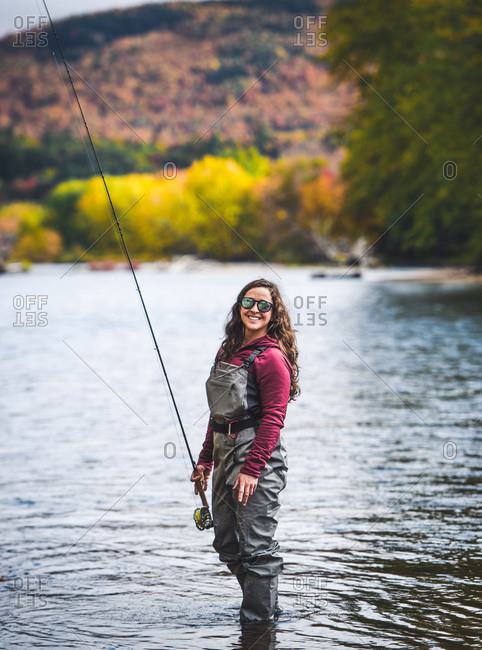Woman in waders standing in river with fall foliage behind