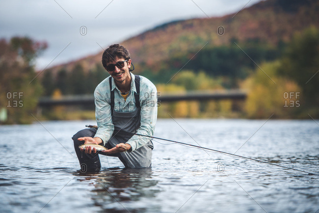 Man holds rainbow trout in river with foliage in background