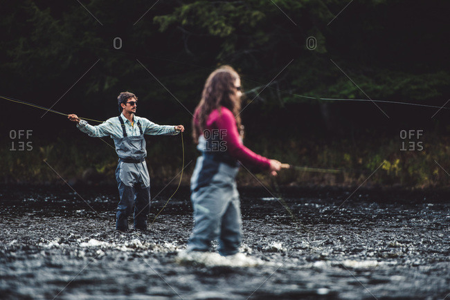 A man and a woman fish in a river with a dark background