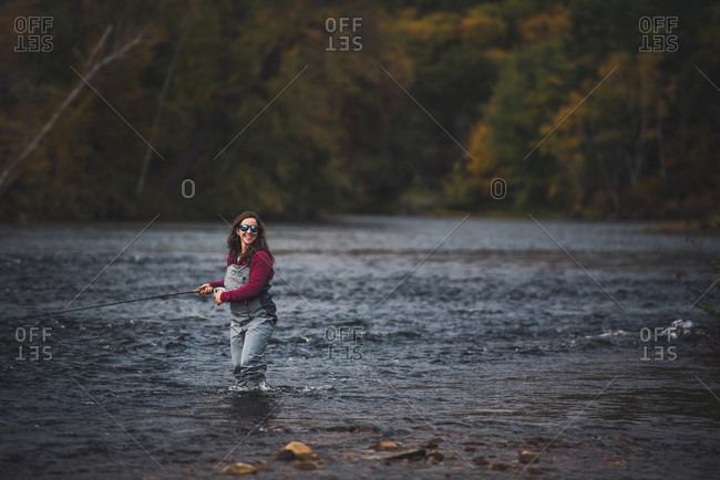 Woman angler walking through water with fly rod and foliage