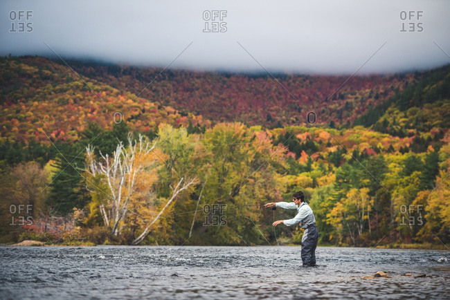 Fly fisherman casting into river with clouds and bright foliage