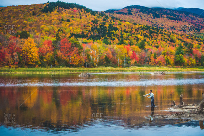Fly fisherman casting into river with bright foliage and mountains