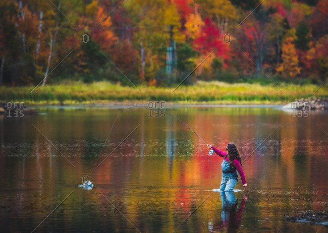 A woman angler catches a fish during fall foliage season