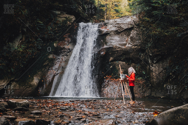 Woman Painter Artist Painting A Picture Close to a Waterfall