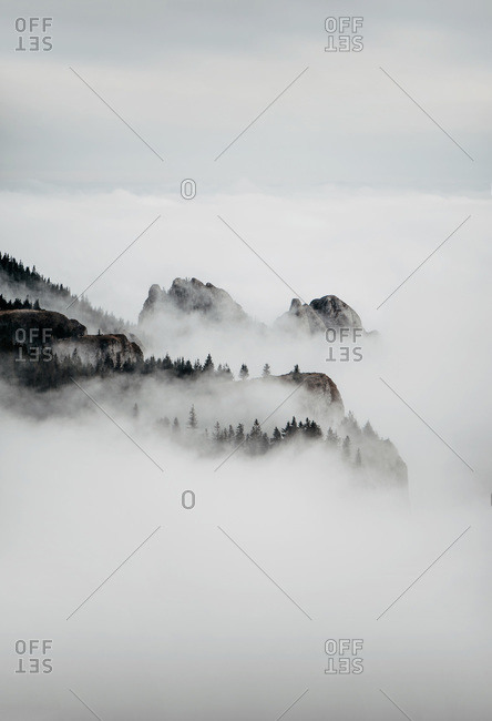 Silhouette of Mountains Covered in Fog During Winter