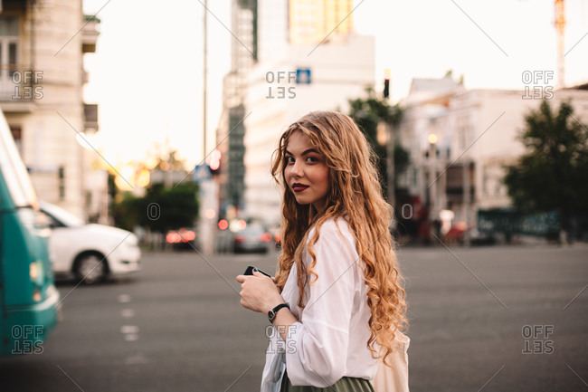 Portrait of serious young woman standing on street in city