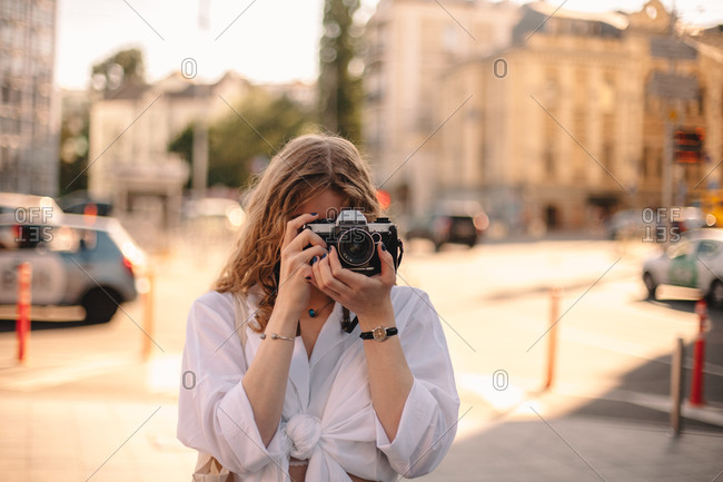 Young woman photographing while standing on street in city in summer