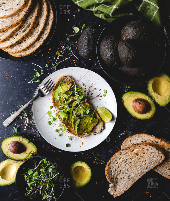 Avocado toast on a plate with ingredients around it on black counter.
