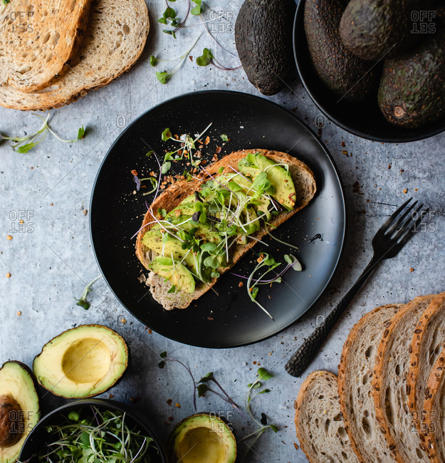 Avocado toast on a plate with ingredients around it on stone counter.