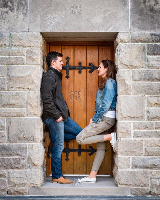 Caucasian couple standing in doorway of stone building together.