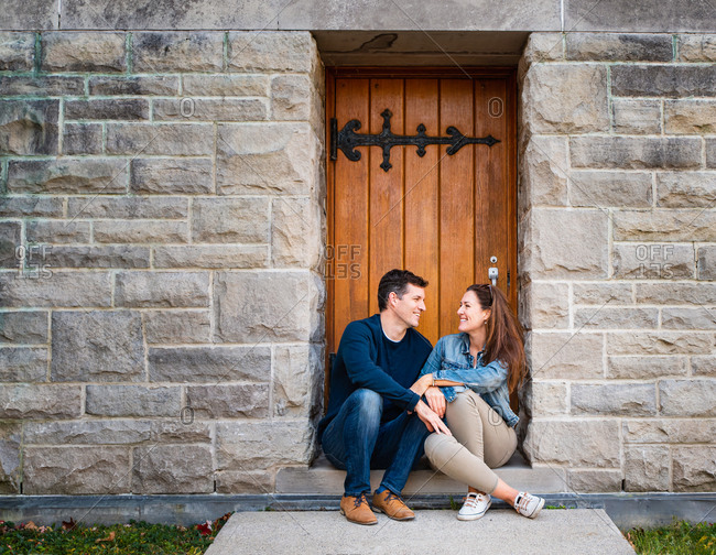Caucasian couple laughing while sitting in doorway of stone building.