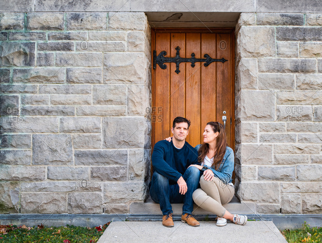 Caucasian couple sitting in doorway of stone building together.