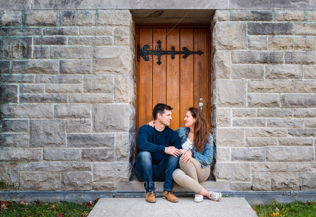 Couple look at each other while sitting in doorway of stone building.
