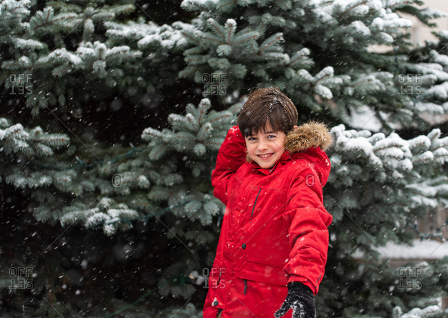 Cute boy in red winter jacket throwing snowball on snowy day outside.