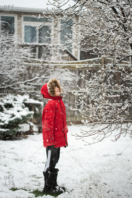 Boy in red winter jacket standing outside in a yard on a snowy day.