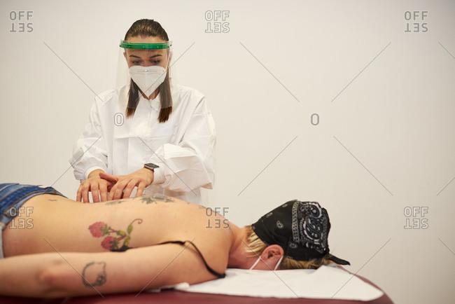 Masseur massages a woman's back.