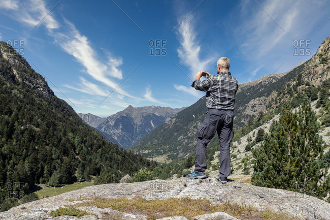 Male middle aged tourist take pictures with mobile phone in Spanish Pyrenees mountain in a sunny day