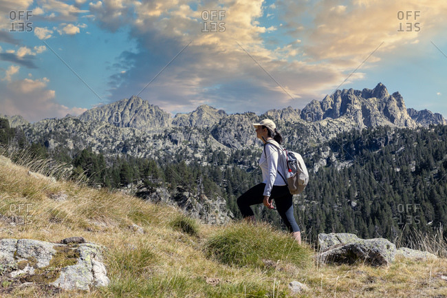 Female middle aged Spanish tourist walking by Spanish Pyrenees mountain during sunny day