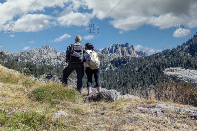 Middle aged tourist couple looking forward to landscape, Mountain Pyrenees of Spain