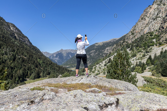 Female middle aged tourist take pictures with mobile phone in Spanish Pyrenees mountain in a sunny day
