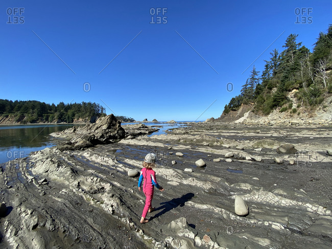 A young girl walks on the shore at low tide on the coast of Oregon.