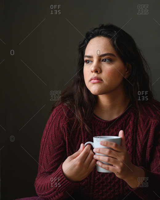 Close shot of a beautiful young brunette woman drinking tea at home