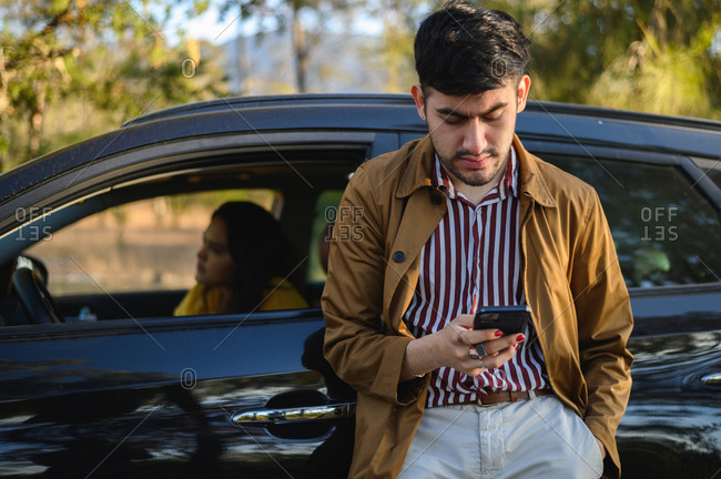 Man using his cellphone during a road trip with his girlfriend.