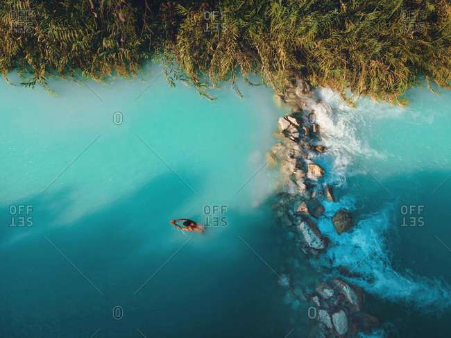 Aerial drone view of man swimming in tropical blue hot springs river