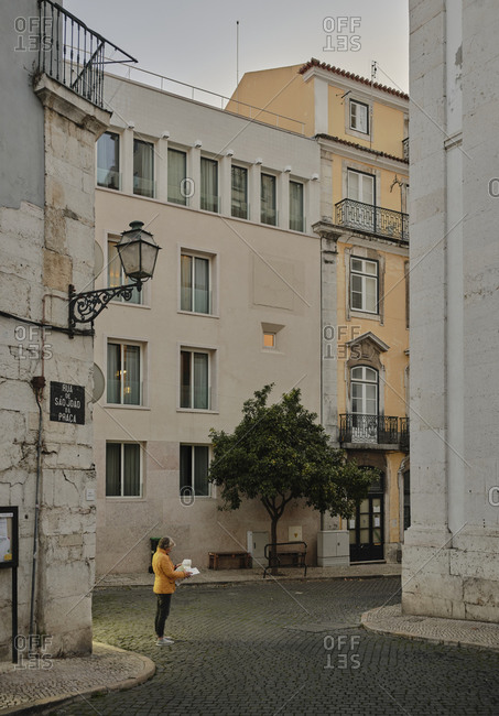 Lisbon, Lisbon, Portugal - October 19, 2019: Female tourist looking at map on street in Alfama