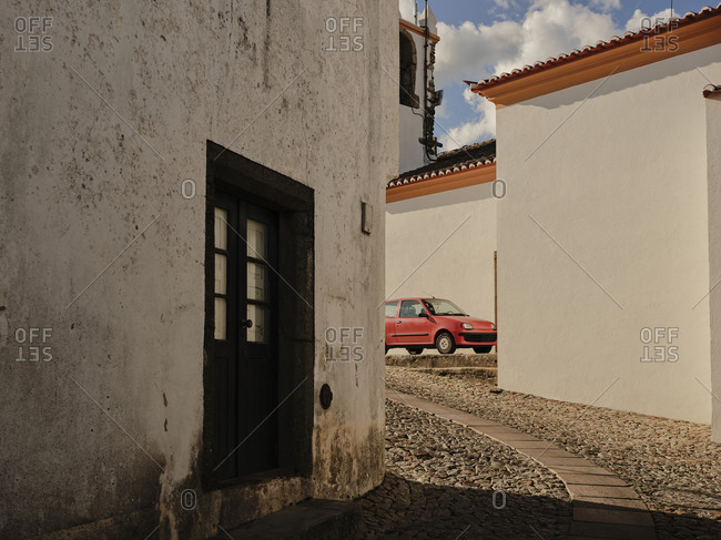 Old compact orange car parked in town of Marvao