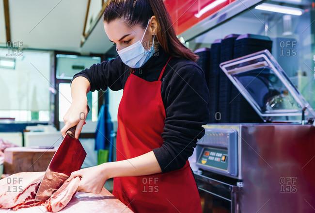 butcher woman cutting a good beef steak