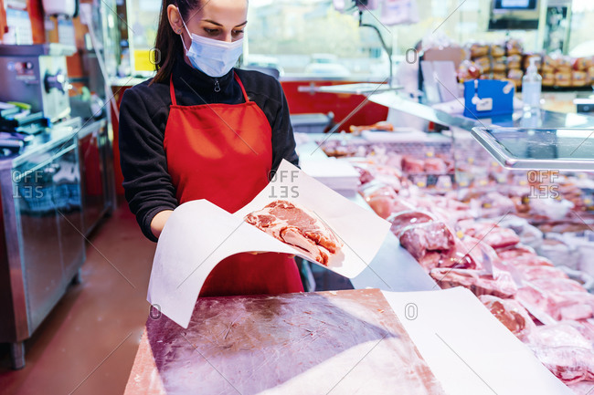 butcher woman packing beef steaks