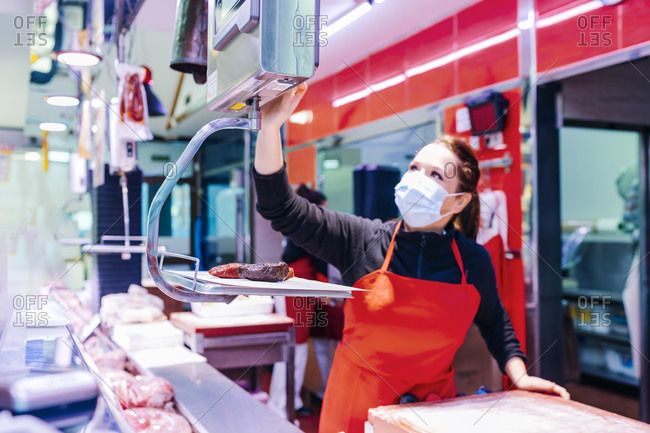 butcher woman weighing meat on the scale