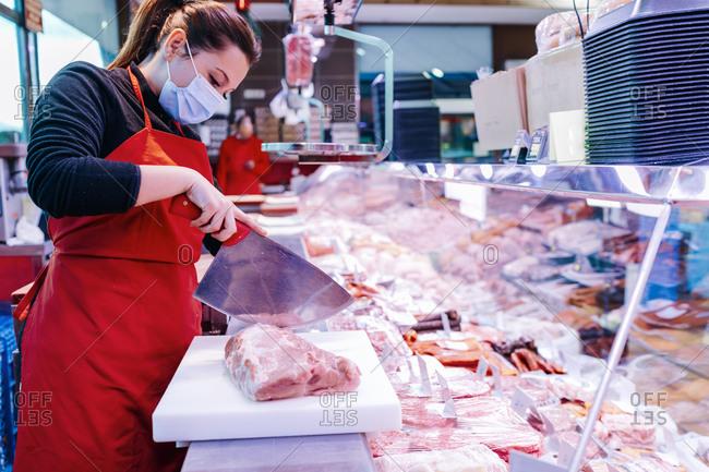 butcher woman cutting a pork fillet