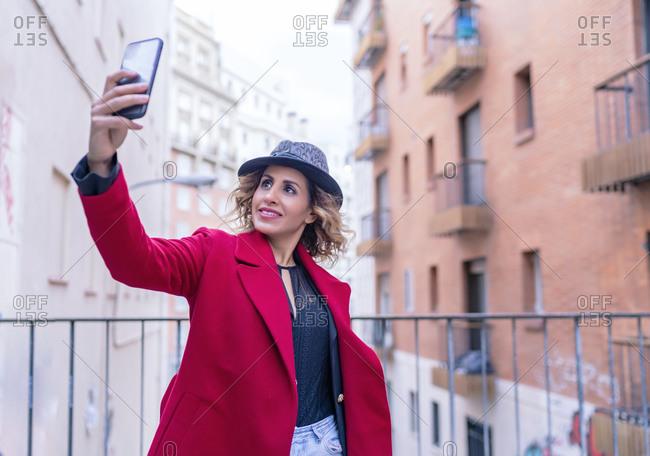 woman in red jacket taking a selfie