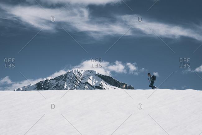 Piedrafita de Jaca, Aragon, Spain - August 21, 2020: Young man walking mountain a snowed ridge against snowcapped peak