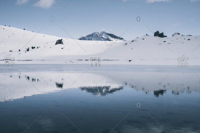 Snowcapped mountain reflection a half frozen lake in the Pyrenees, Pan